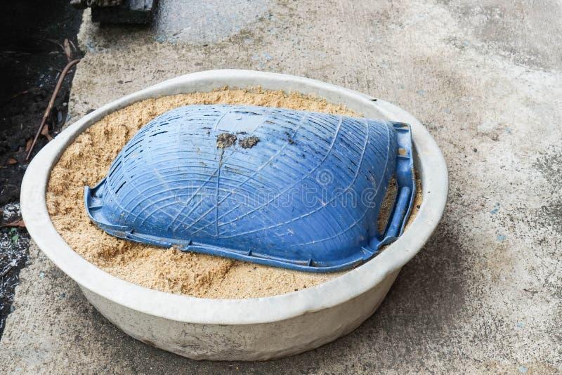 煤斗和沙子在不锈的桶在水泥地板上 免版税库存照片