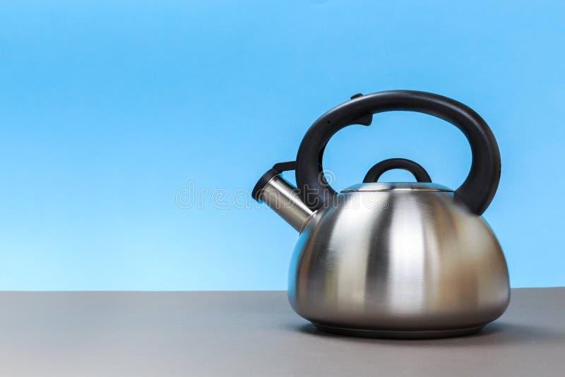 煤气炉的一个新的金属水壶在一张灰色桌上 免版税库存照片