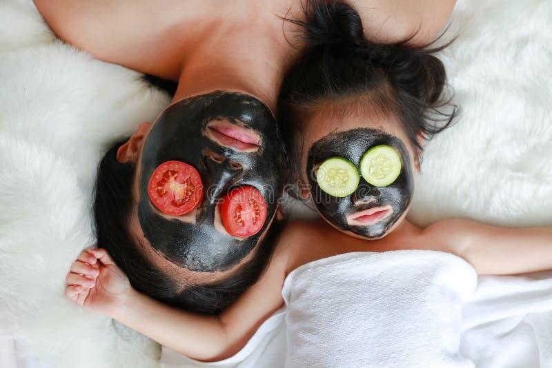 煤炭削皮拿着在眼睛的面罩的少妇和儿童女孩蕃茄和黄瓜切片,秀丽概念 免版税库存照片
