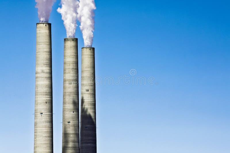煤炭厂污染概念的烟窗反对清楚的蓝色的 免版税库存照片
