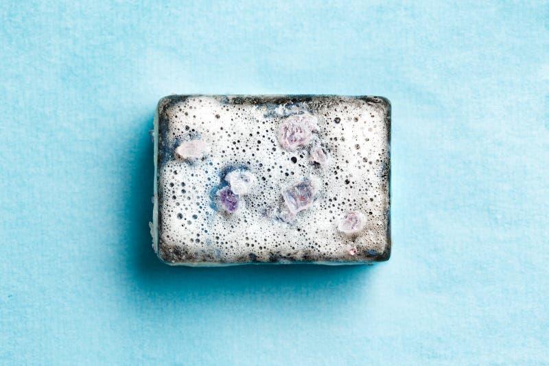 黑煤炭肥皂在泡沫的在蓝色背景 库存照片
