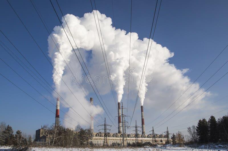 从煤电植物的高污染 反对太阳的黑烟 复杂的工厂厂房抽烟的烟囱  航空 库存图片