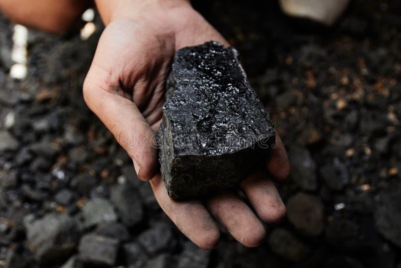 煤矿工人在煤炭背景的人手上 联合矿业或e 图库摄影