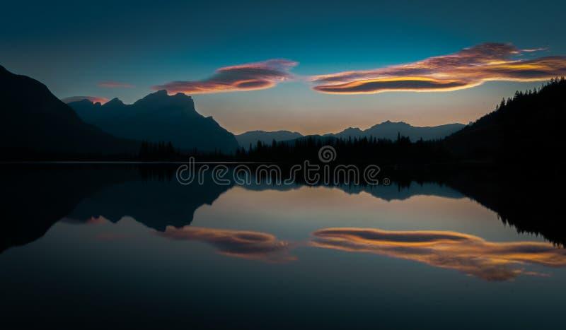照亮一个对在银朱的湖镇静水反射的橙色和桃红色,B的蓬松云彩的早日出 库存照片