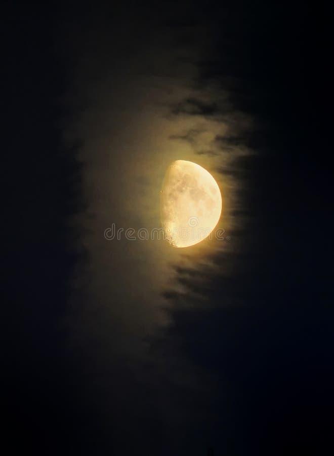 照亮一朵通过的云彩在黑暗的天空的发光的月亮 免版税库存图片