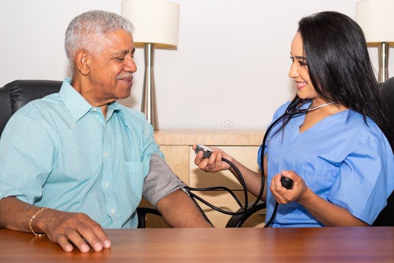 照料一名年长患者的护士在家 免版税库存图片