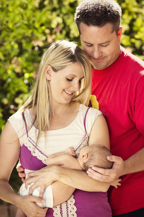 照料新的婴孩的年轻父母 库存照片