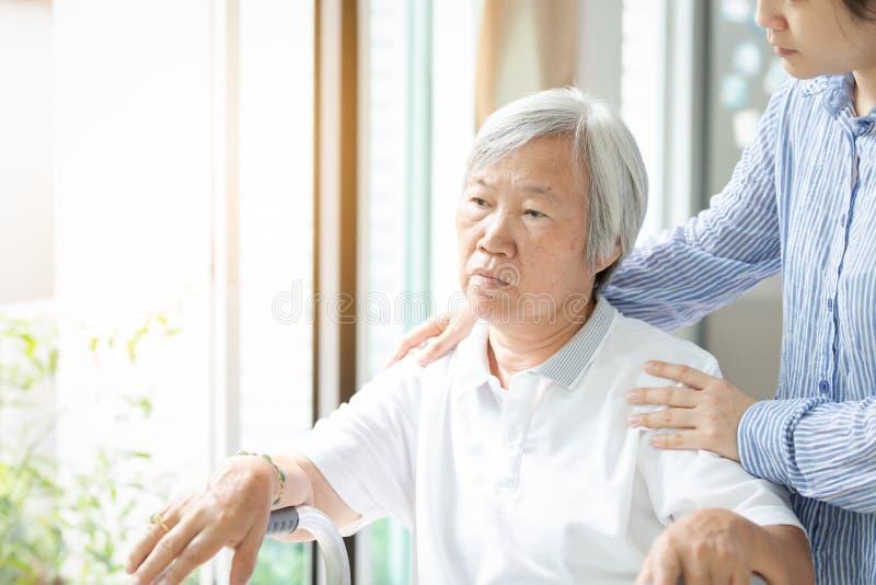 照料者亚裔女儿或年轻护士身分在看窗口用手的资深妇女后在老妇人的肩膀, 免版税图库摄影