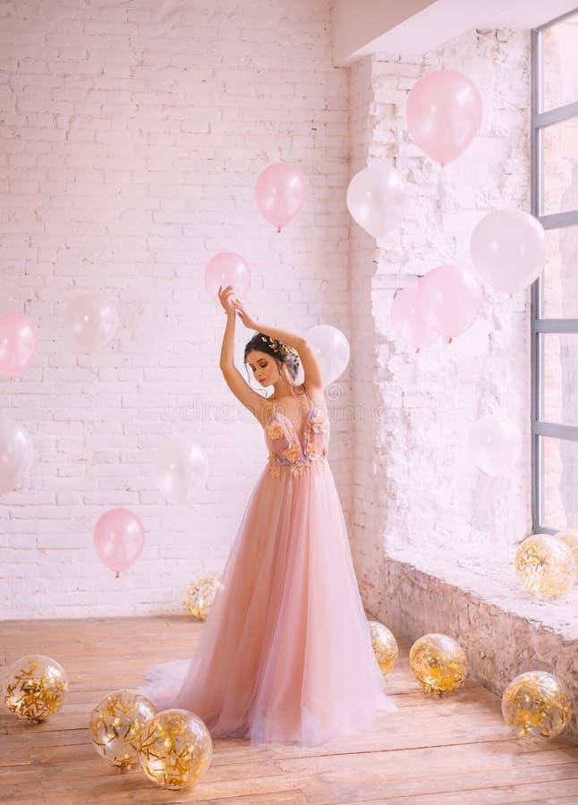 照片中止片刻,有黑发的一俏丽的少女在与一件紫色礼服的一个桃子在站立并且跳舞 免版税库存图片