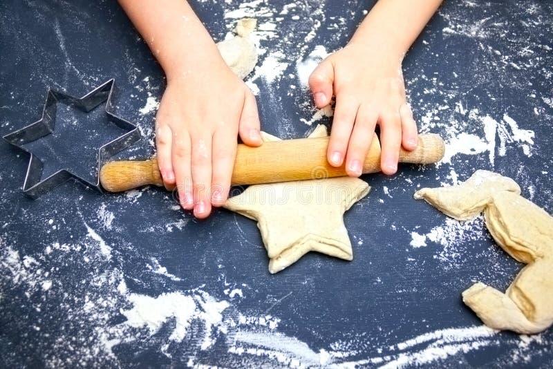 照片从上面孩子` s手、一些面粉、麦子面团和辗压别针在黑桌上 揉星d的儿童手 免版税库存图片