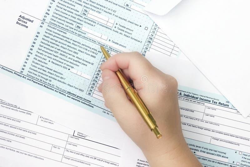 照片从上面报税表1040 签署或填装形式的妇女 1040所得税形式 顶面veiw,有选择性的软的foc 免版税库存图片