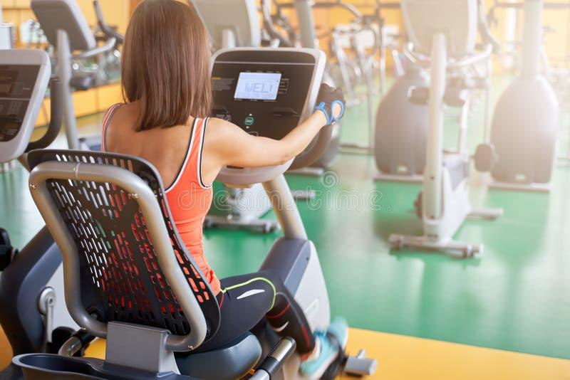 照片体育妇女坐一辆固定式自行车,做心脏锻炼,踩的踏板,测量脉冲 免版税库存照片