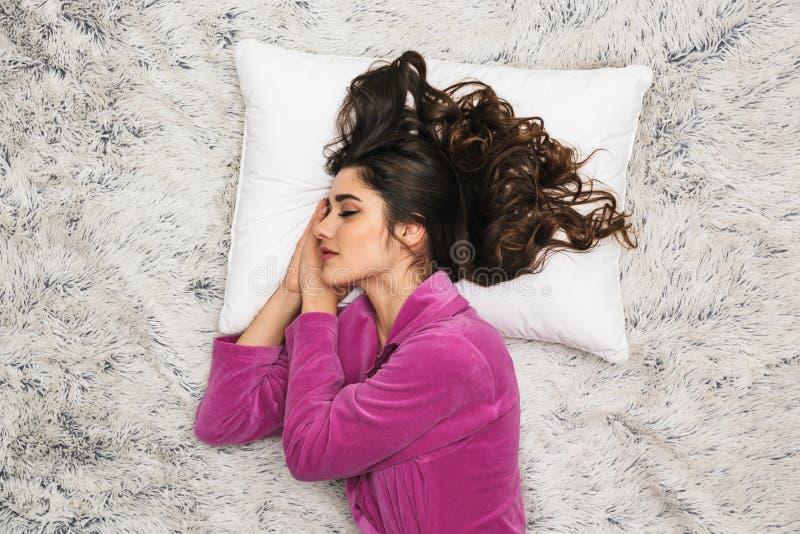 照片佩带少女家常服的从上面深色的妇女说谎和睡觉在公寓的白色毛皮 免版税库存图片