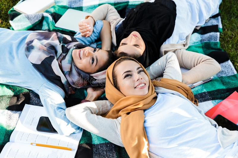 照片头戴头巾的从上面美丽的伊斯兰教的妇女说谎在毯子在绿色公园 库存图片