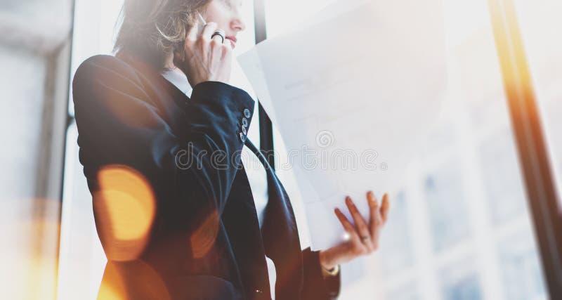 照片女商人佩带的白色衬衣,谈的智能手机和举行文件在手上 露天场所顶楼办公室 全景胜利 免版税库存照片