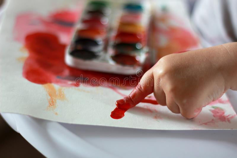 照片孩子画在红色油漆的一个手指在纸 在油漆的手 反对水彩油漆背景 库存图片