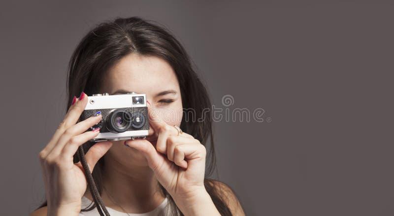 照片射击 拍与葡萄酒减速火箭的照相机的年轻美丽的女性摄影师照片 库存图片