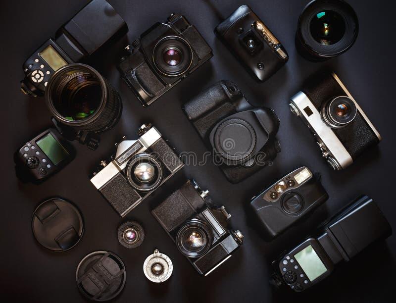 照片工作场所概念 汇集葡萄酒影片和数字照相机,在黑背景,顶视图 库存图片