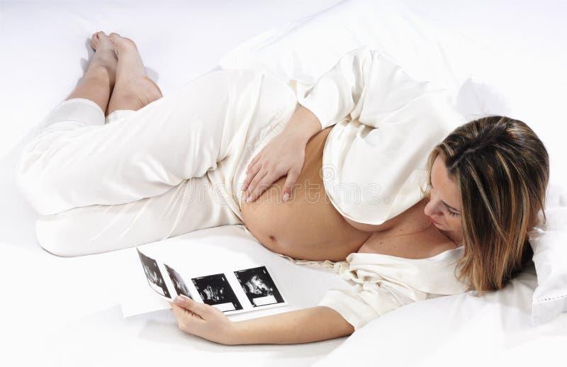 照片怀孕的超声波注意的妇女 免版税库存图片