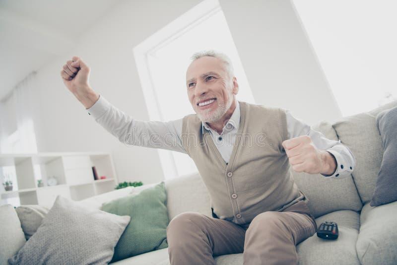 照片惊奇的关闭质朴他他年迈的人注意到的他体育相配的比赛成就武装的手提高了空气穿戴白色 免版税库存照片