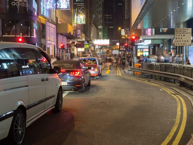 照片拍与行人交叉路的一张缓慢的快门速度在中央的皇后大道 免版税库存照片