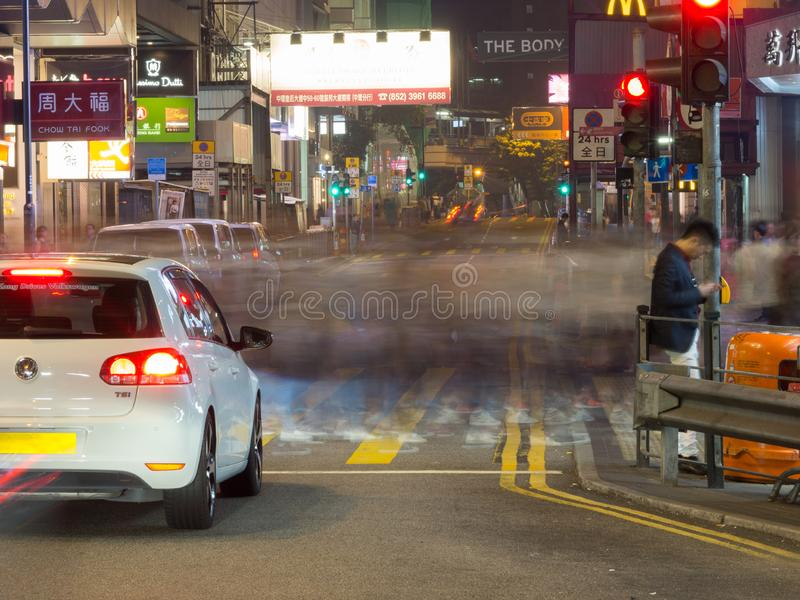 照片拍与行人交叉路的一张缓慢的快门速度在中央的皇后大道 免版税库存图片