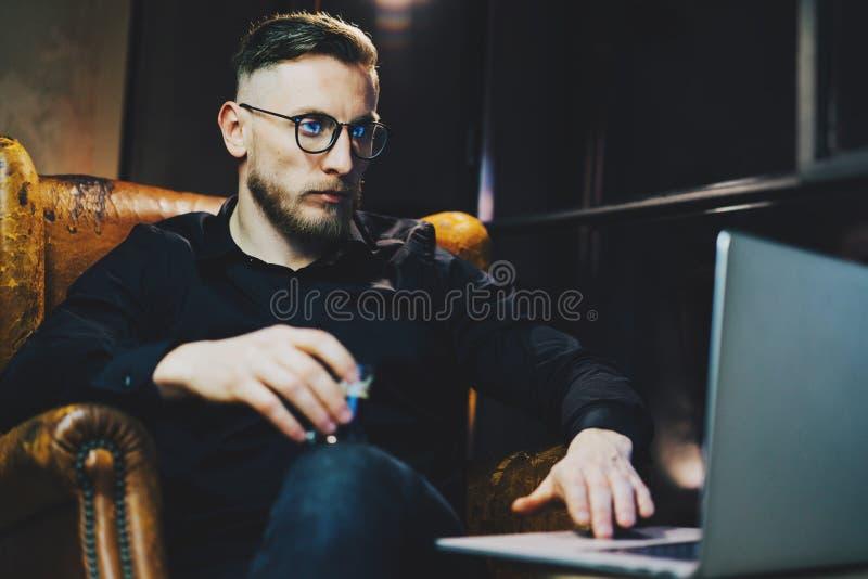 照片时髦的银行家松弛现代顶楼办公室在工作天以后 坐在葡萄酒椅子的人在晚上 使用 库存图片