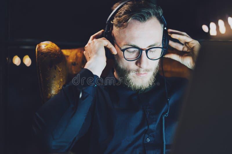 照片有胡子的商人松弛现代顶楼办公室 供以人员坐在葡萄酒椅子,听的音乐膝上型计算机 使用 库存照片