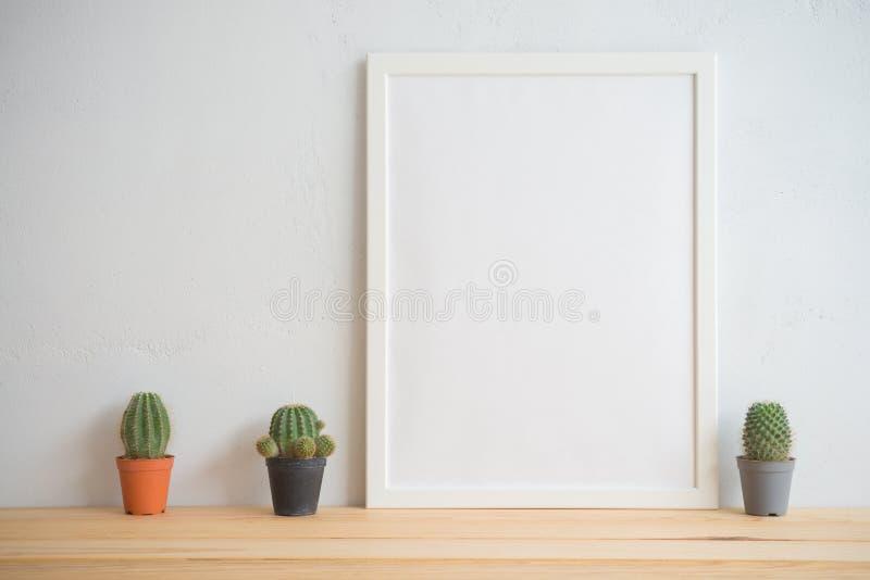 照片框架和仙人掌罐大模型有白色墙壁背景, c 图库摄影
