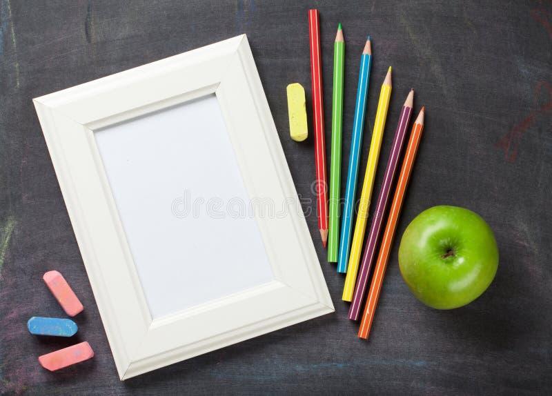 照片框架和学校用品在黑板背景 免版税图库摄影