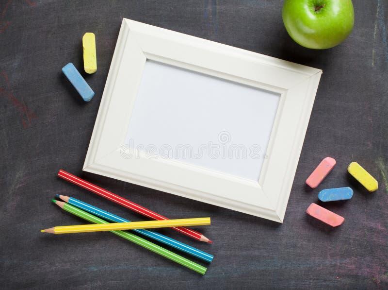 照片框架和学校用品在黑板背景 图库摄影