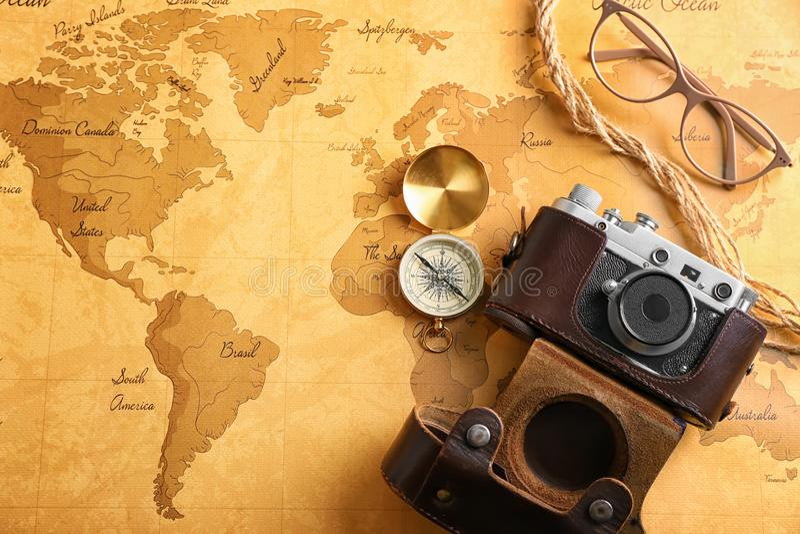 照片照相机、指南针和玻璃在葡萄酒世界地图 r 免版税库存图片
