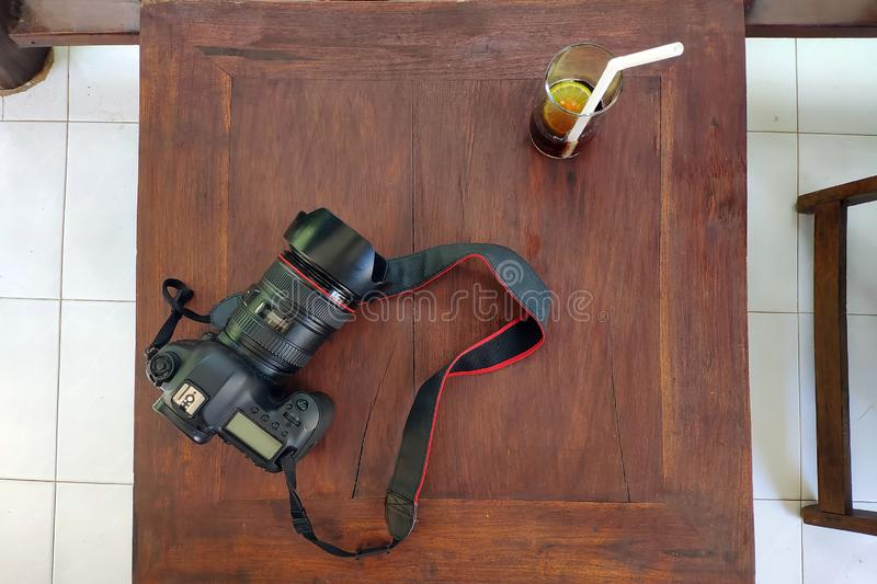 照片照相机和杯可乐用在一张木桌上的柠檬 室外平的位置 库存照片