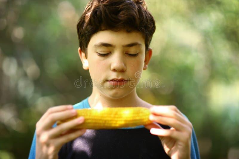 照片的少年男孩吃煮沸的玉米棒子关闭 免版税库存照片