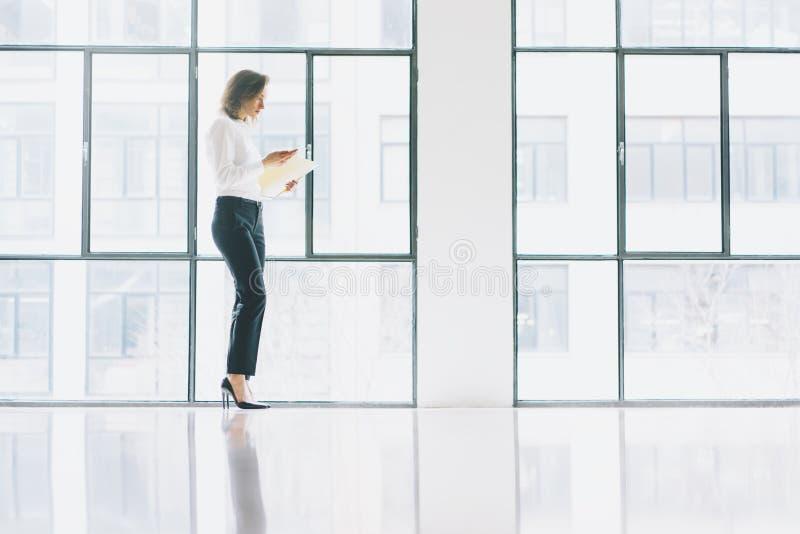 照片穿着现代衣服,看起来手机和在手上的女商人拿着纸 露天场所顶楼办公室 免版税库存照片