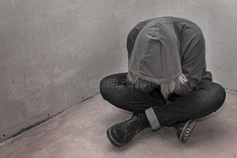 照片绝望年轻吸毒者佩带的敞篷和单独坐在角落 免版税库存照片