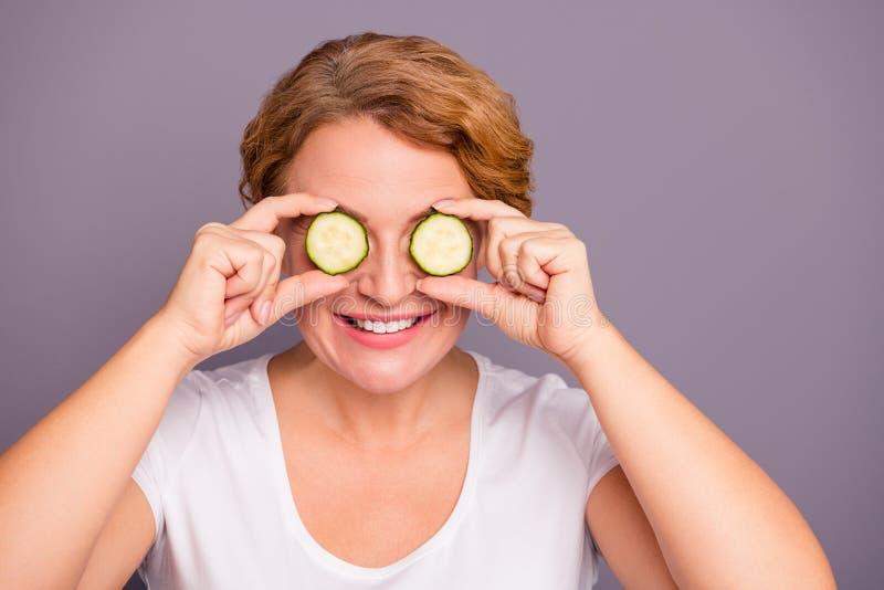 照片美丽惊人成熟的关闭她她的在眼睛自然治疗理想的夫人沙龙温泉做法黄瓜切片 免版税图库摄影