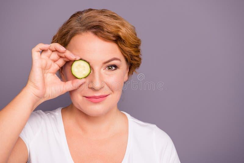 照片美丽惊人成熟的关闭她她的夫人温泉做法举行黄瓜切片皮眼睛自然治疗理想 库存照片