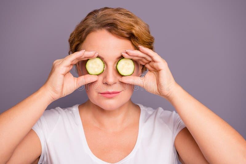 照片美丽惊人成熟的关闭她她的夫人温泉做法拿着黄瓜specs切片掩藏眼睛自然 免版税库存图片