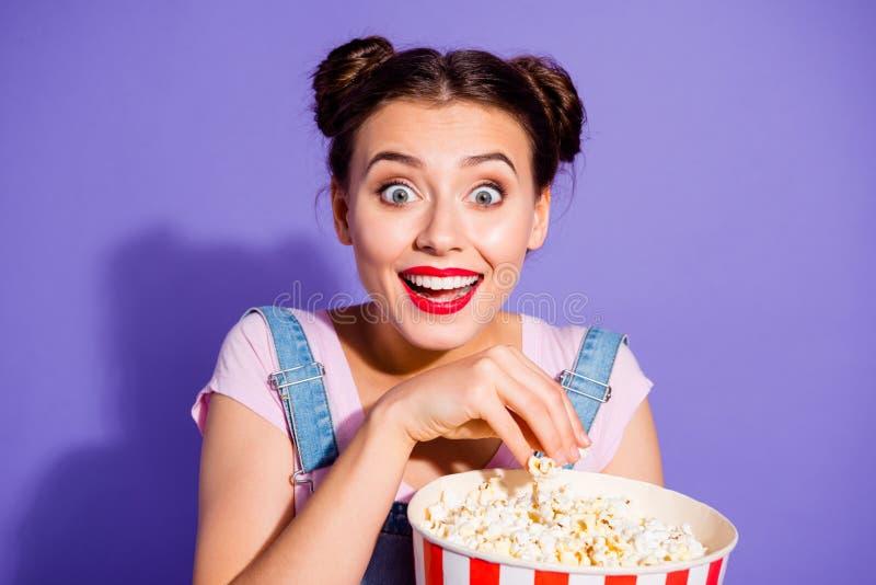 照片美丽惊人的关闭她她的夫人大眼睛质朴的小圆面包观看著名喜剧电视剧举行玉米花桶穿戴 库存图片