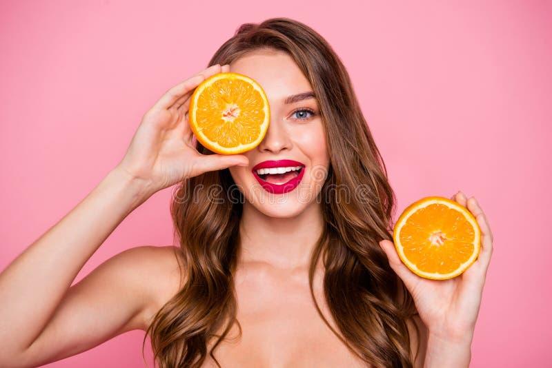 照片美丽惊人的关闭她她的夫人胳膊两个橙色切片掩藏一眼睛完善的魅力嘴唇自然身体关心 免版税库存图片