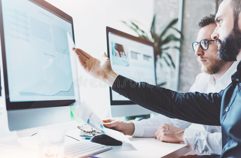 照片运作的过程 显示报告屏幕的财务商业经理 年轻企业乘员组与现代起始的项目一起使用 库存图片