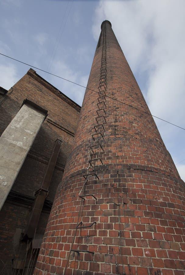 照片,有铁的老砖工厂烟囱托看对夏天蓝色多云天空的台阶步 库存照片