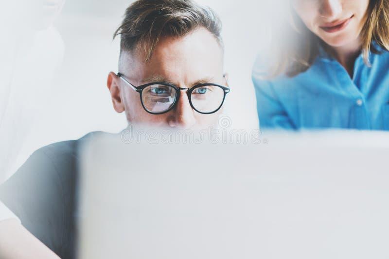 照片年轻帐户经理与同事新的项目一起使用 队工作 分析在膝上型计算机的计划 被弄脏的背景 库存照片