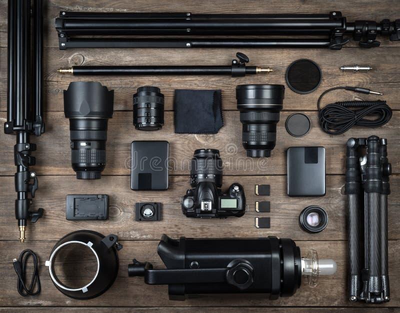 照相机和摄影设备透镜,三脚架,过滤器,闪光,存储卡,坚硬书桌,在木书桌上的反射器的套 免版税库存图片