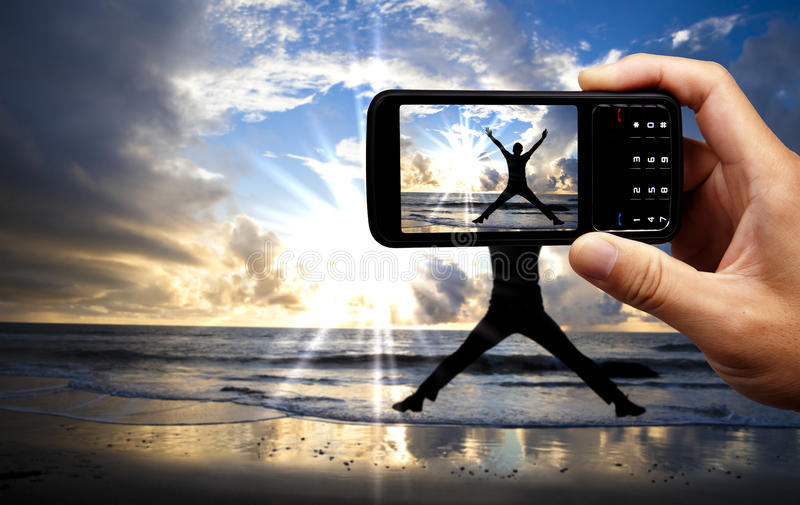 照相机愉快的跳的人移动电话 免版税库存照片