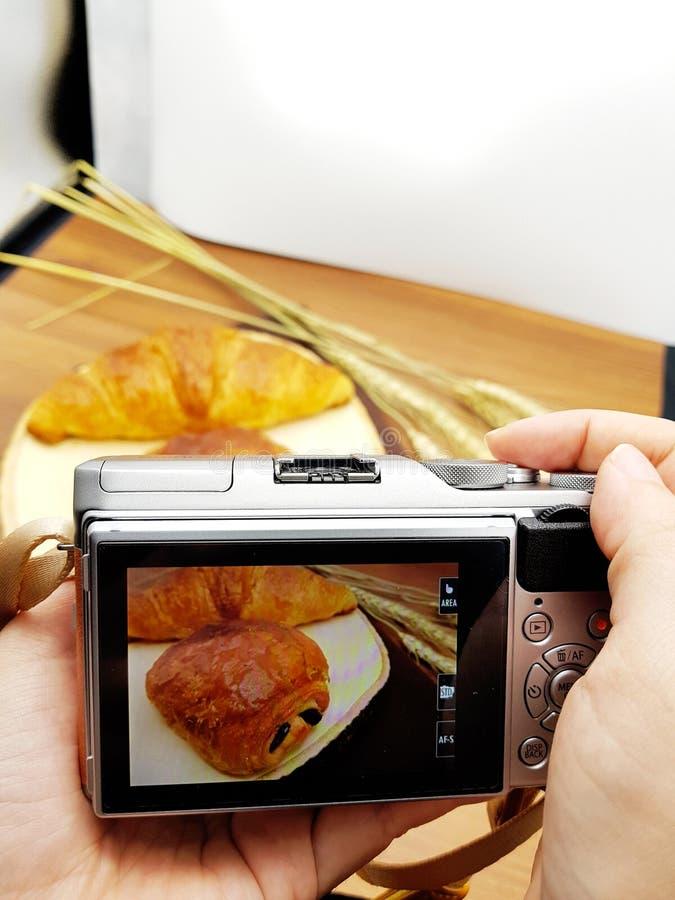 照相机捕获美味的酥皮点心:在土气背景的巧克力新月形面包 库存图片