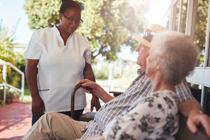 照看一对年长夫妇的护工 免版税图库摄影