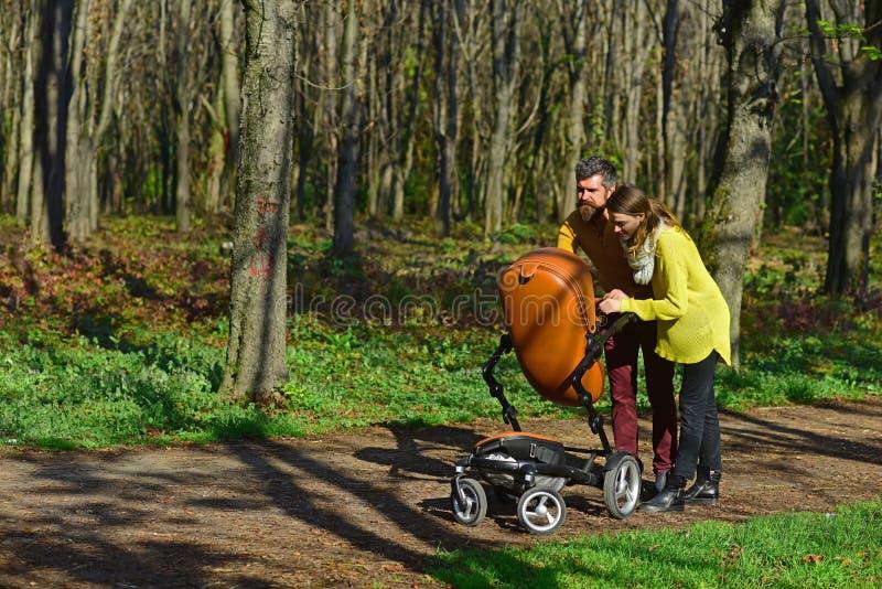 照看小孩服务 有胡子的看顾与婴孩摇篮车的男人和俏丽的妇女在春天公园 婴幼儿保育服务为 库存图片