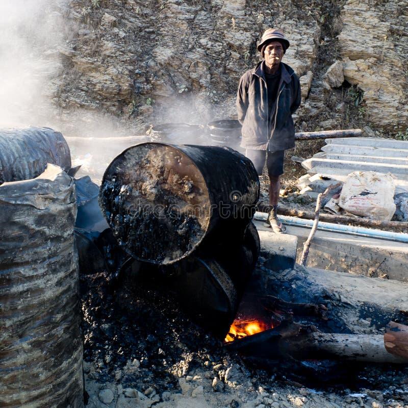 照看沥青燃烧的工作者 库存图片
